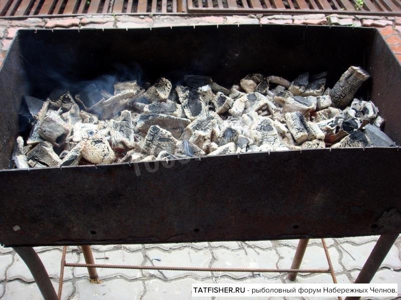 Рыба на костре на решетке на углях